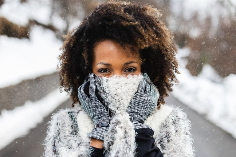 A black woman with a scarf and afro standing in the snow.