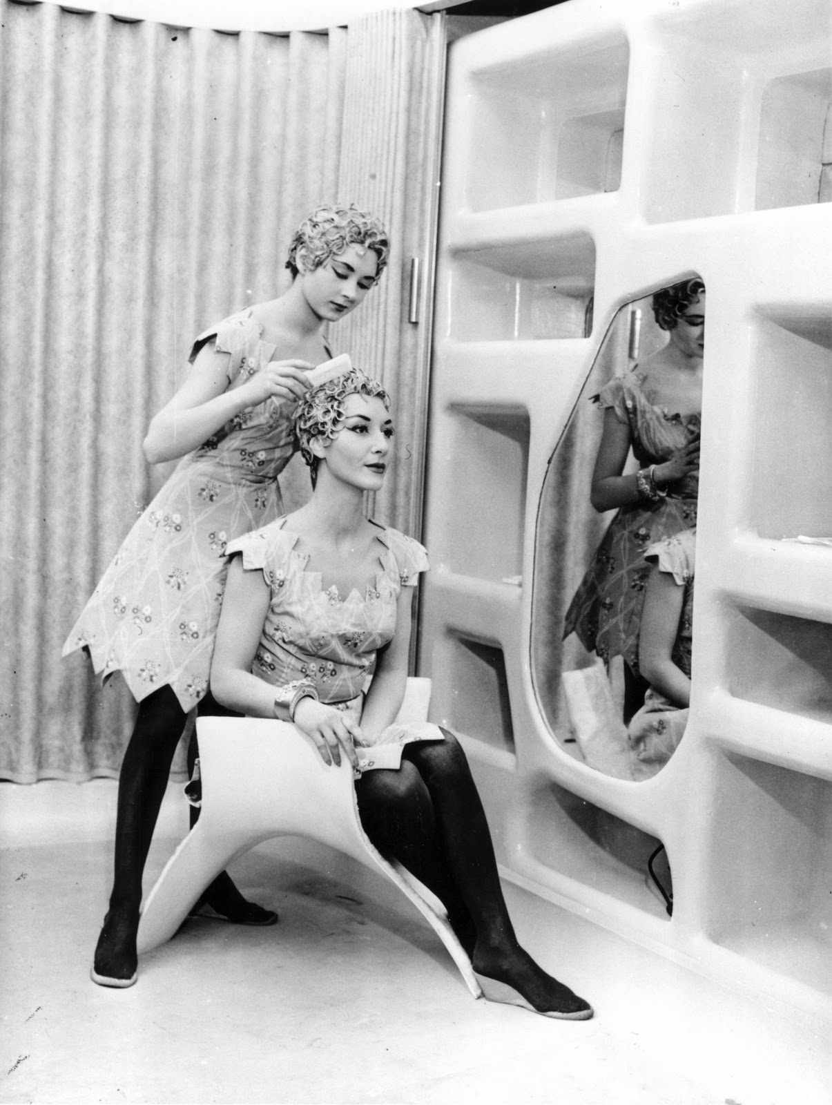 A woman fixing another woman's hair in a dressing room