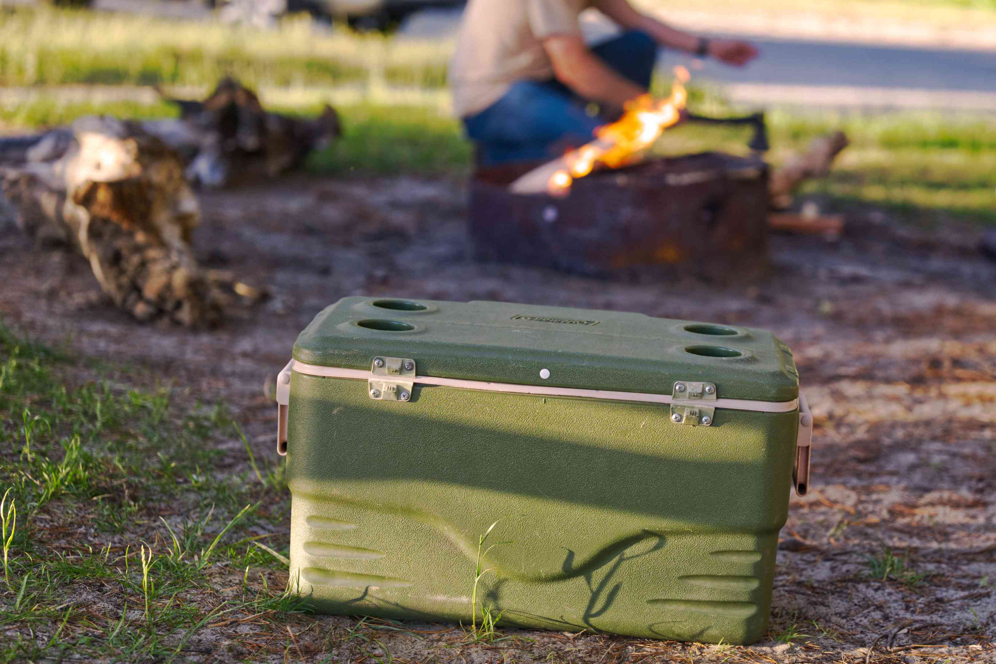 army-green plastic cooler sits in dirt while guy makes fire in campsite firepit