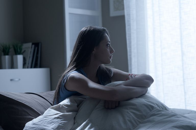 woman sitting up in bed with insomnia