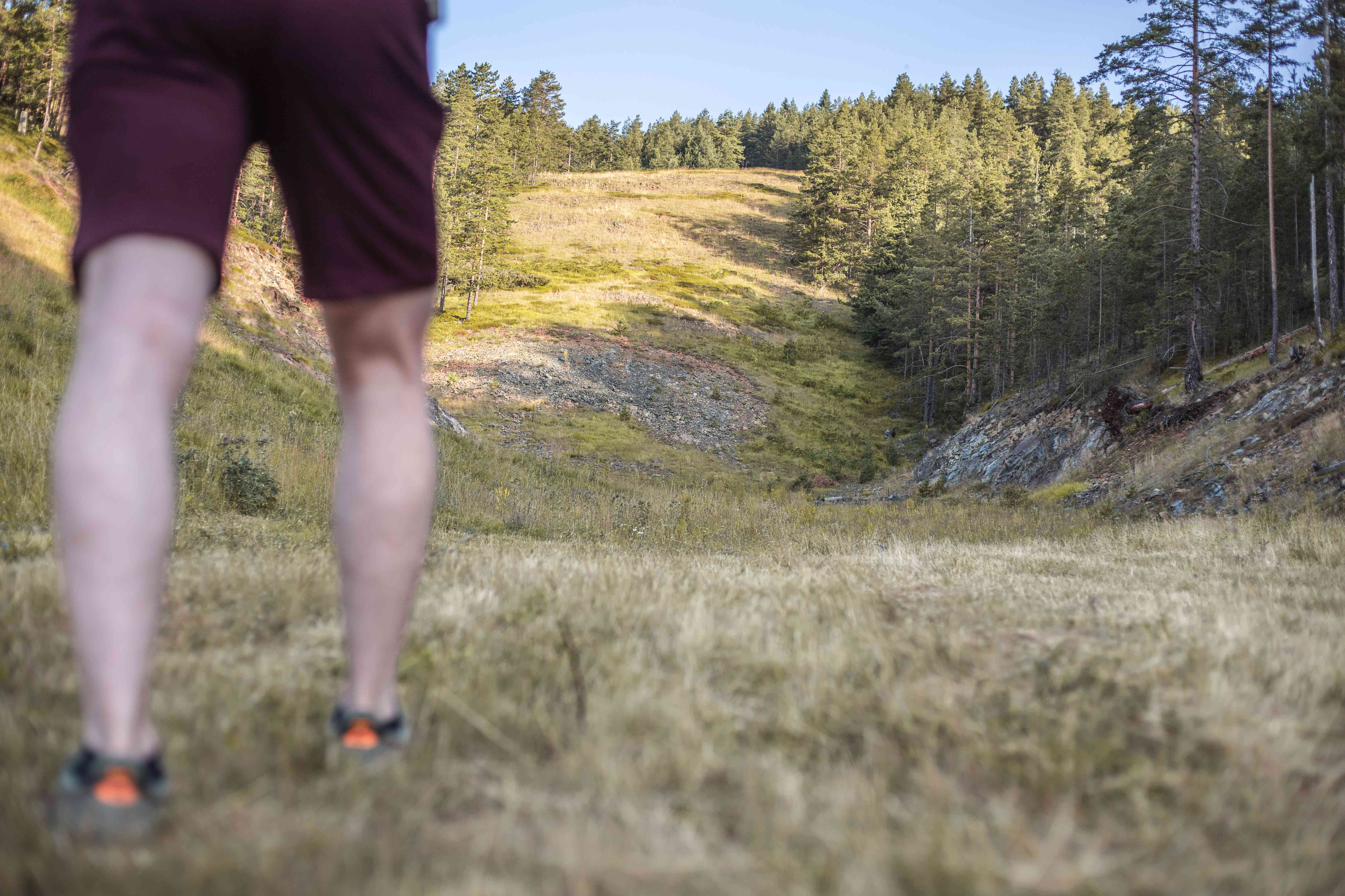 guy in shorts prepares to walk up steep incline on wooded, rocky hill