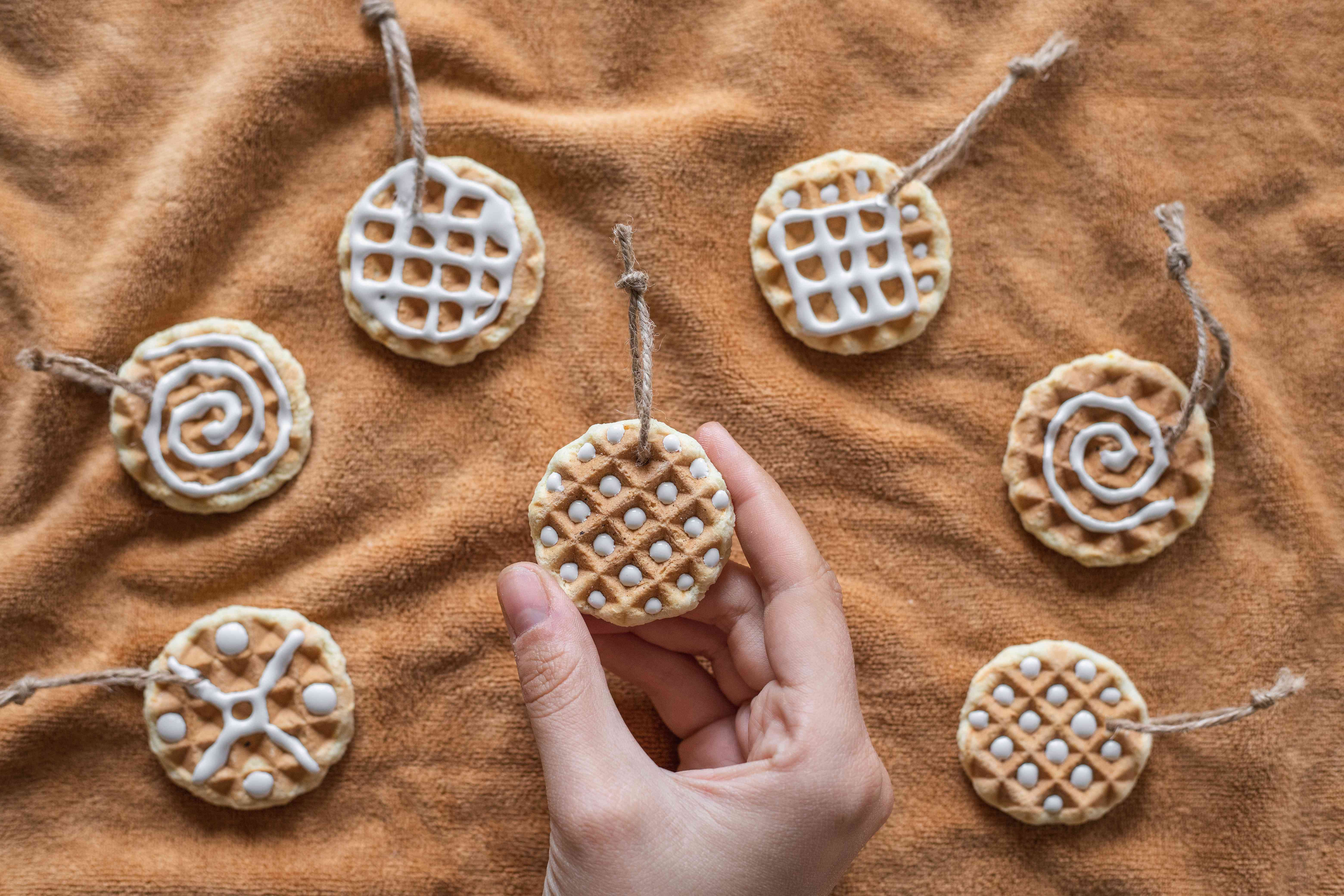 various homemade christmas ornaments made out of expired spices displayed on tan towel