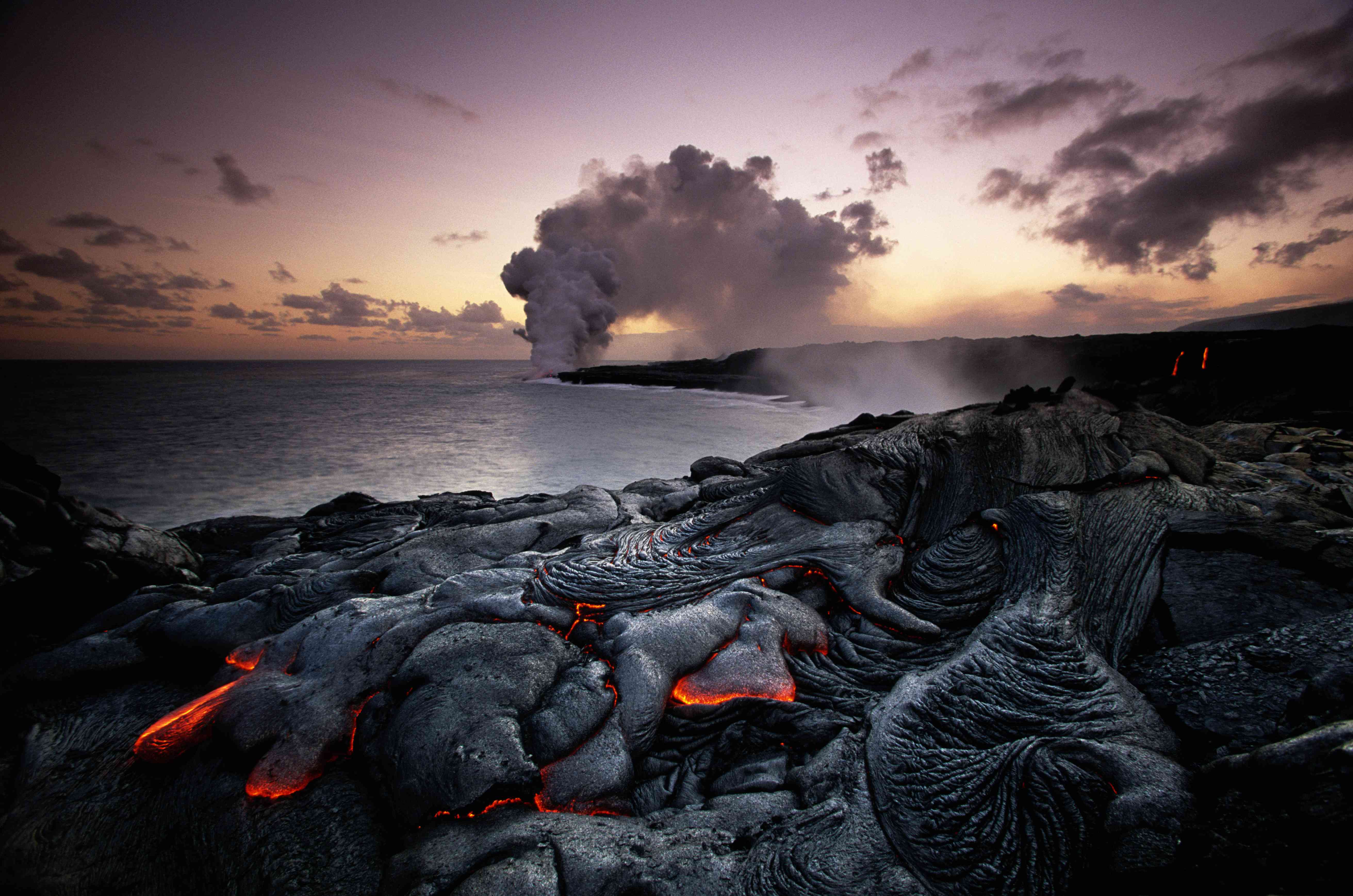 Hot lava on coast with Kilauea erupting in background