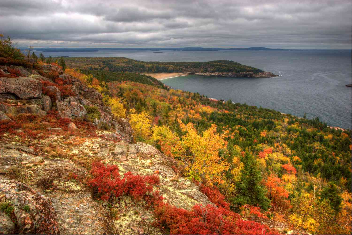 Dark, cloudy skies above the red, yellow, and green of fall with the harbor in the background