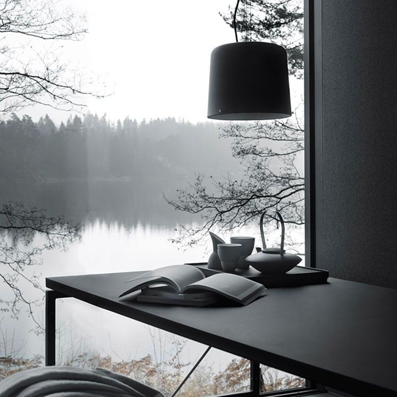 View looking out at a lake from a gray slate table with a lamp hanging