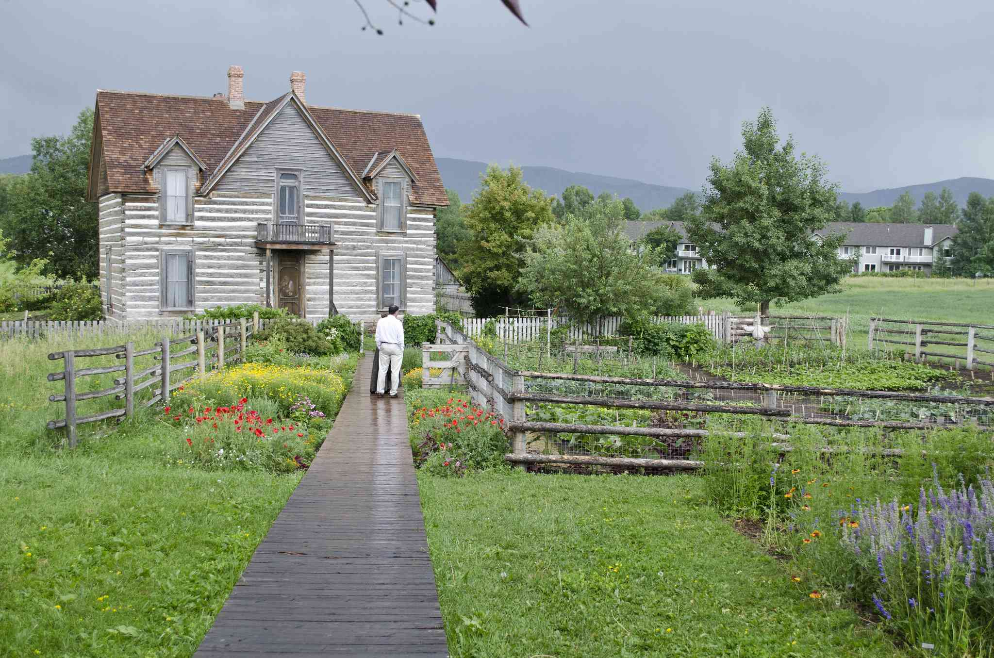 A couple look at the garden in front of a restored farmhouse
