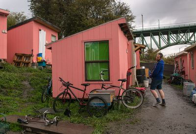 man unloads pink in front of pink tiny house washington