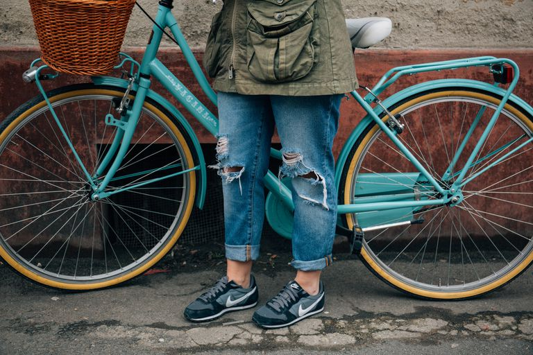 Bottom half of a woman wearing jeans and sneakers, standing next to a teal bicycle with a wicker basket on the front