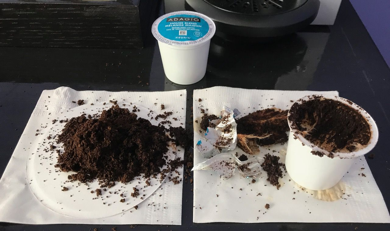 A pile of used coffee grounds next to an opened coffee pod and an unopened one