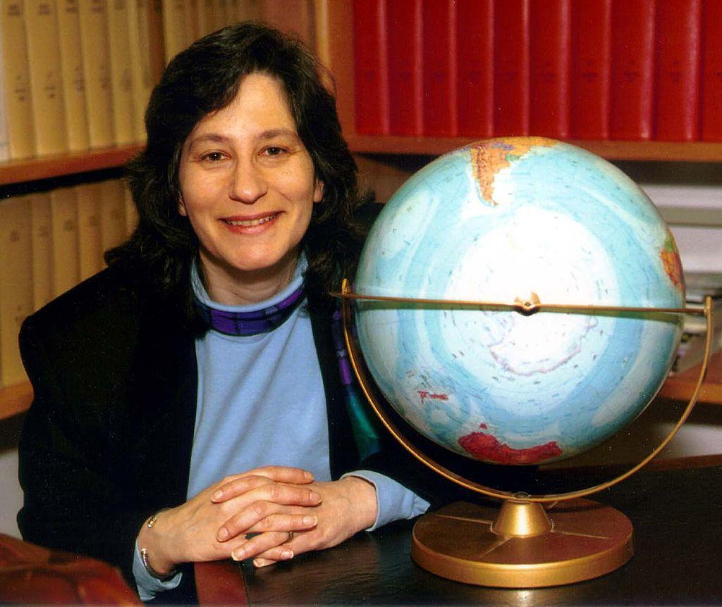 Susan Solomon by a globe
