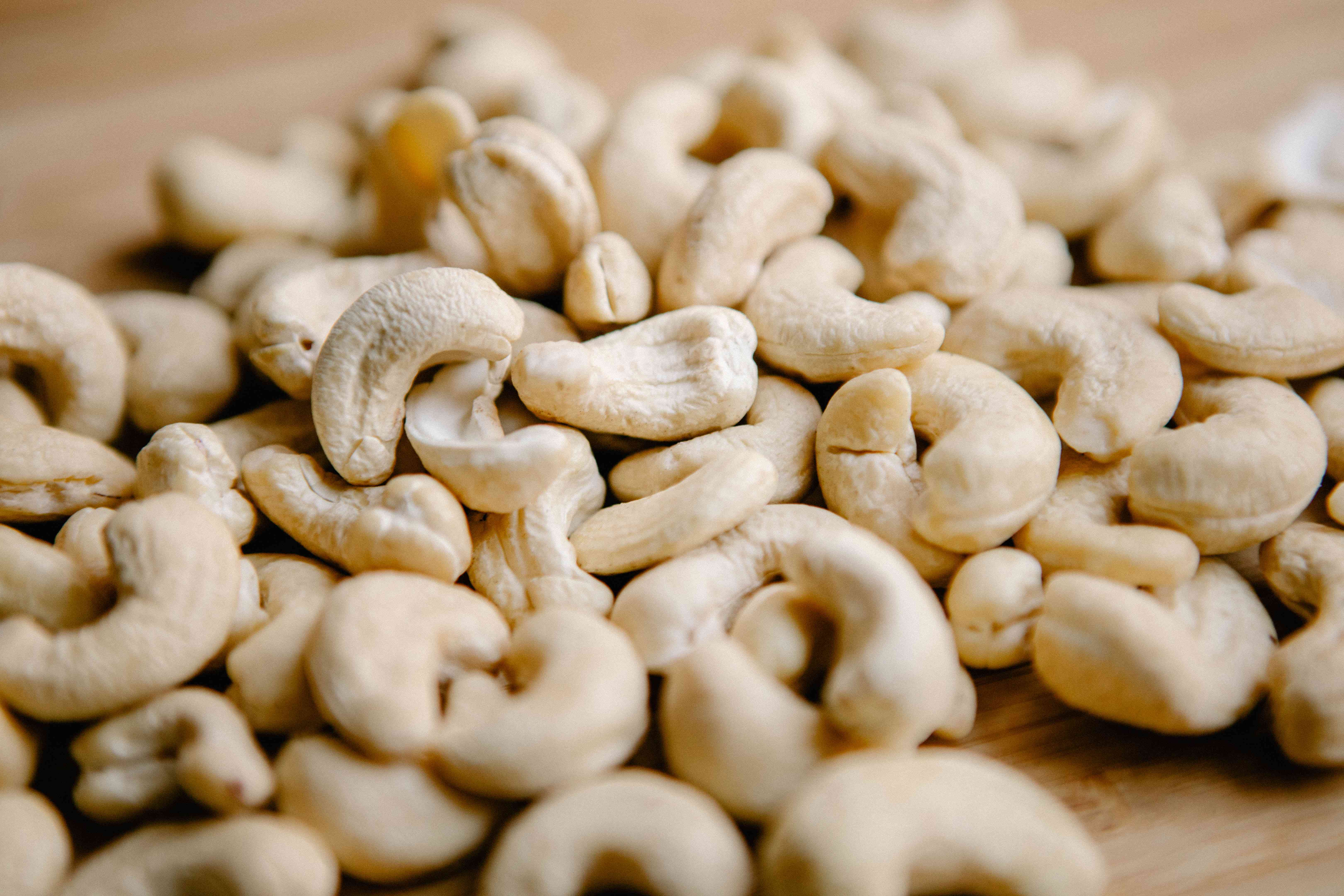 raw cashew nuts on wooden table up close