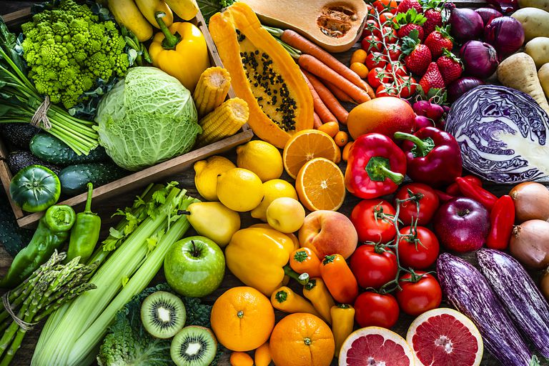 rainbow spread of fruits and vegetables including tomato, purple cabbage, oranges, lemons, celery, and more