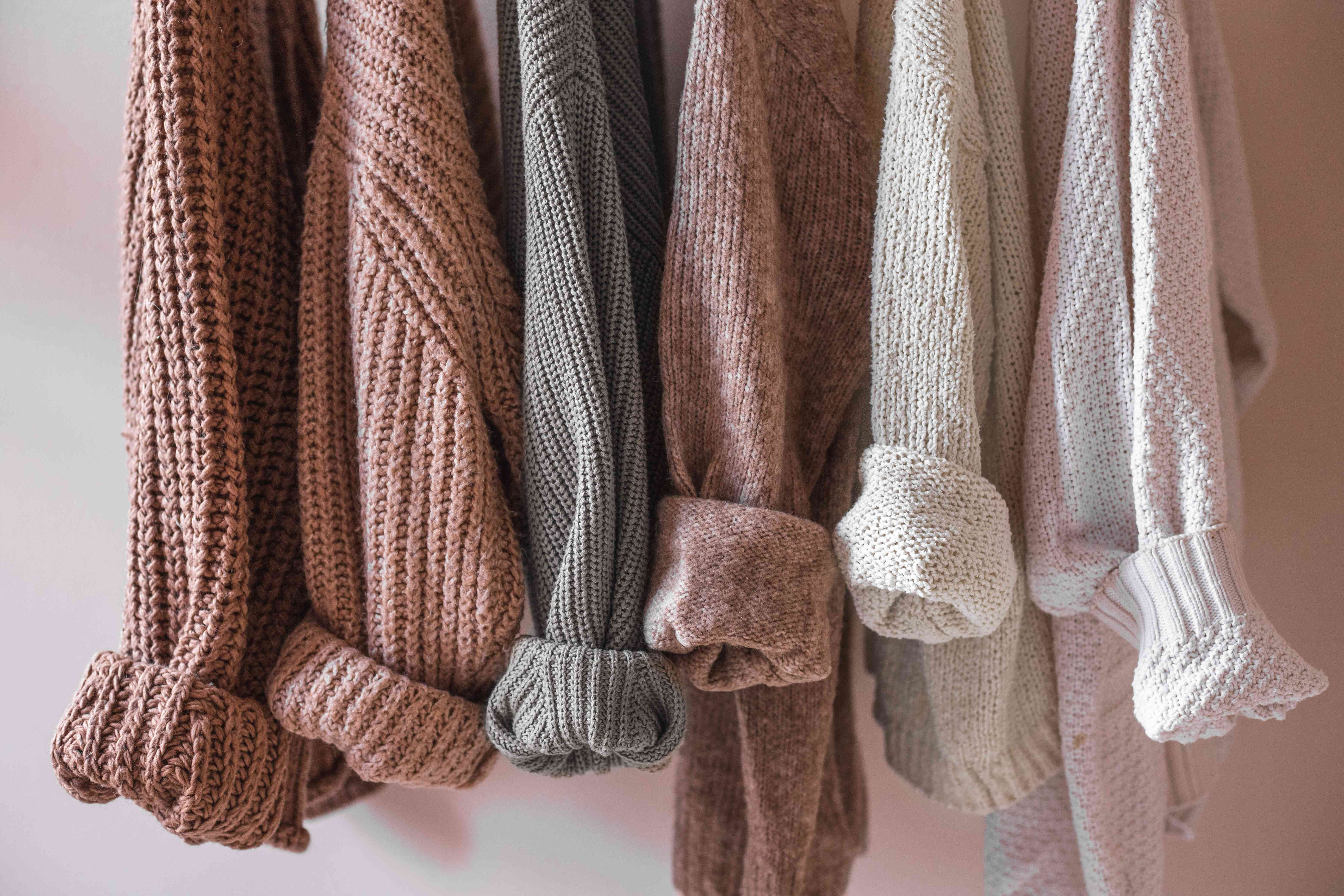 multiple sweaters in earth tone colors hanging with cuffs rolled up
