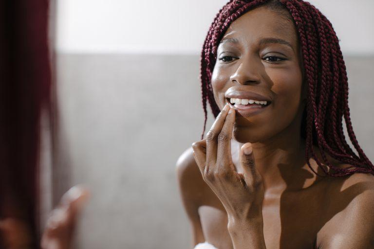 A black woman applies lip balm in the mirror.