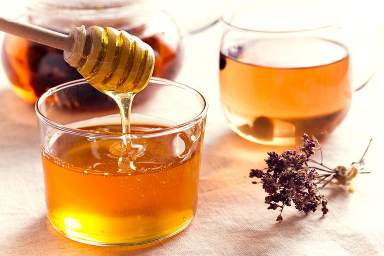 Honey in a glass vase flows down from a wooden spoon.