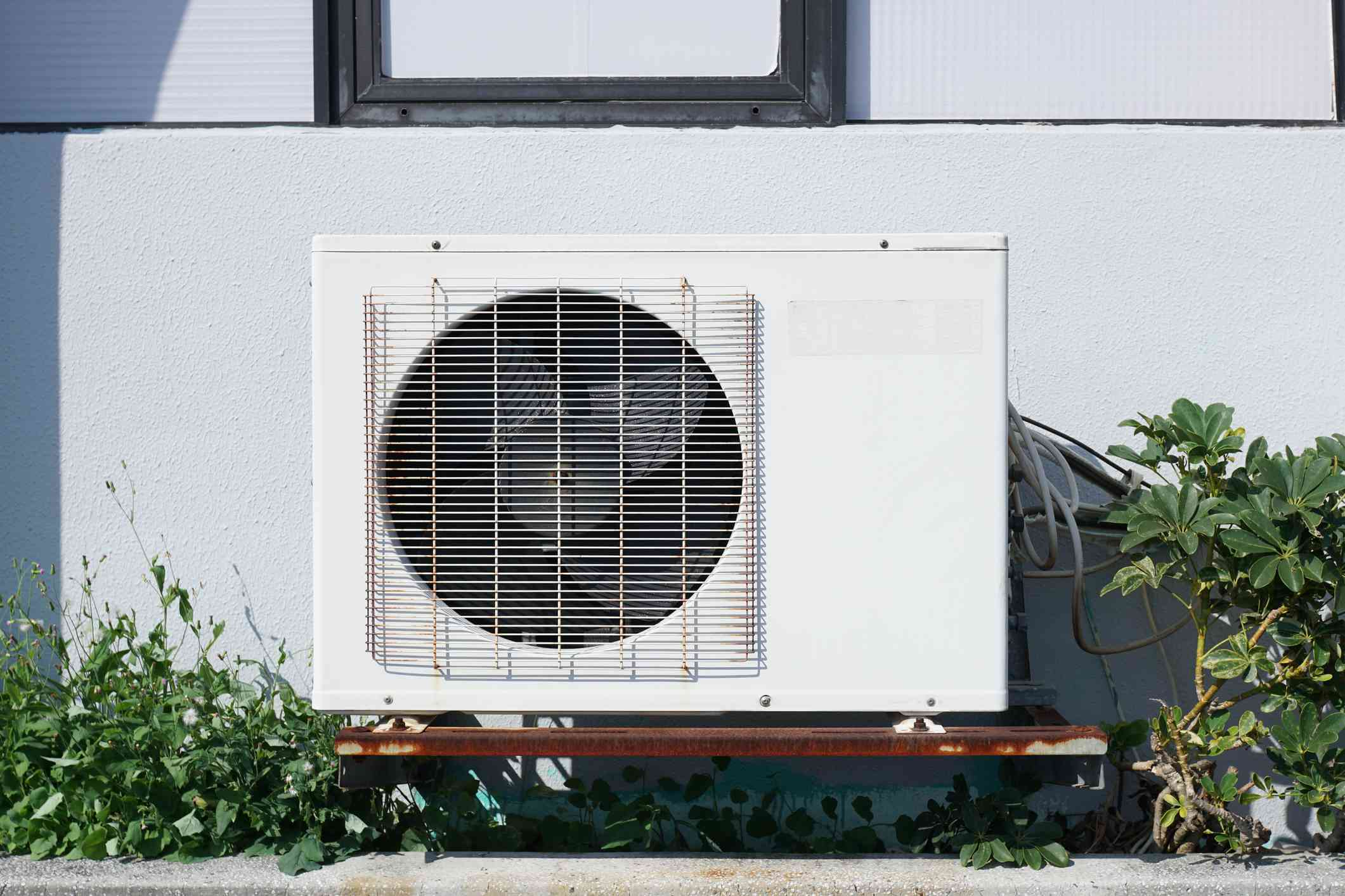 An air compressor next to a building used as part of an air conditioning system.