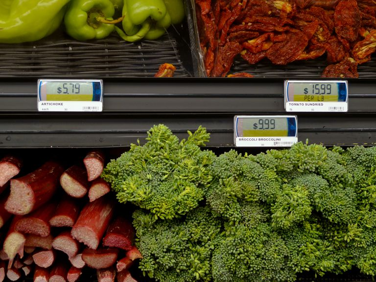 Digital tags in a grocery store displaying prices for vegetables.