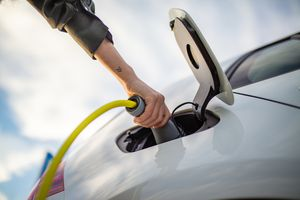 Hand of a woman charging electric car
