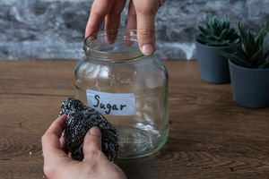 hand uses steel wool scrubby on label