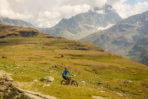 man rides bike over majestic mountains all alone