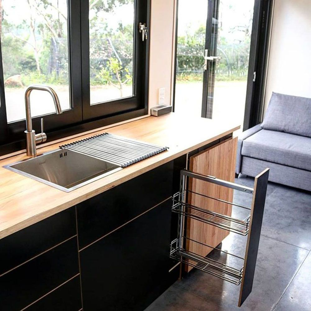 Kitchen sink and open cupboards with a window behind it