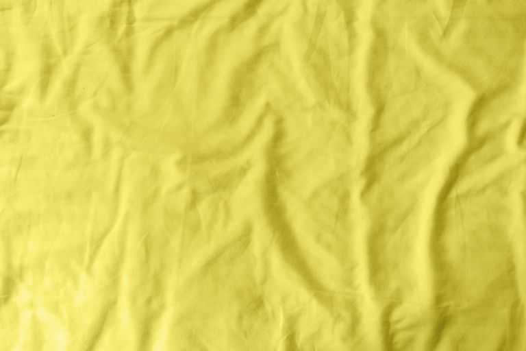 Abstract pattern of a yellow crumpled bed sheet in a hotel room. The manufacturing of bedsheet uses cotton, linen, silk modal and bamboo rayon. Trendy color of year 2021 - illuminatiing yellow