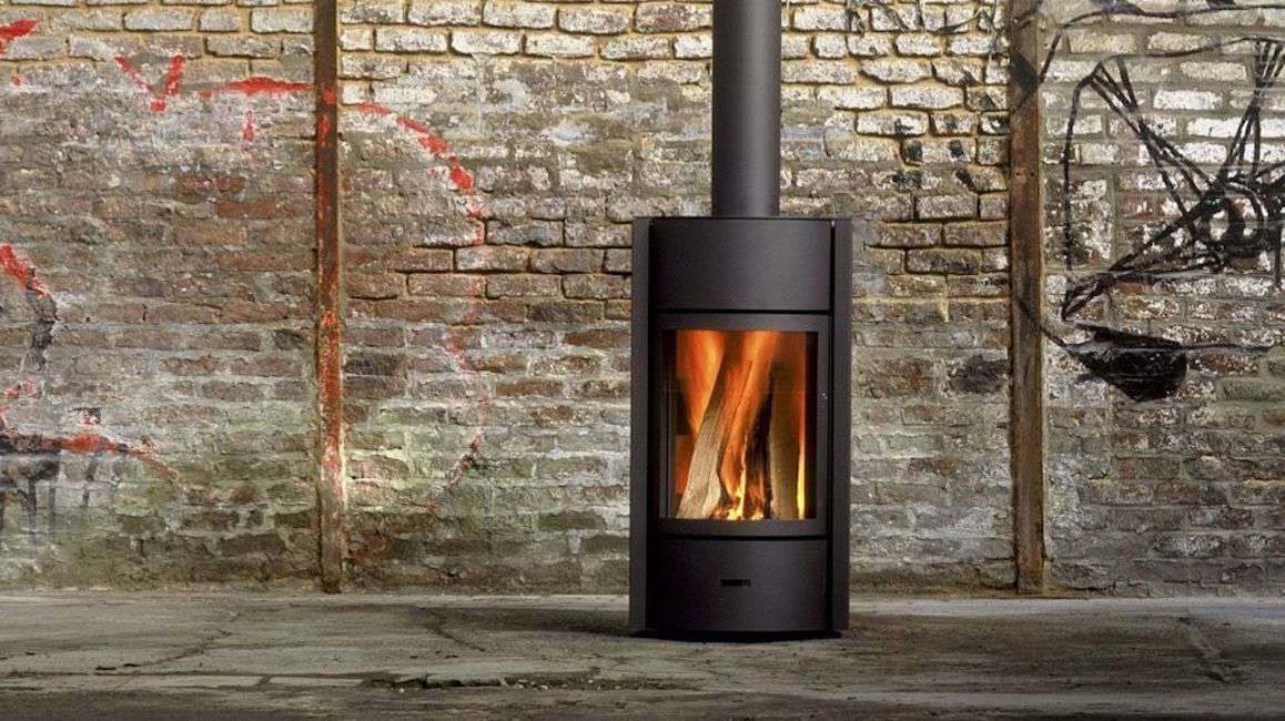 Black vertical wood stove against a graffitied brick wall