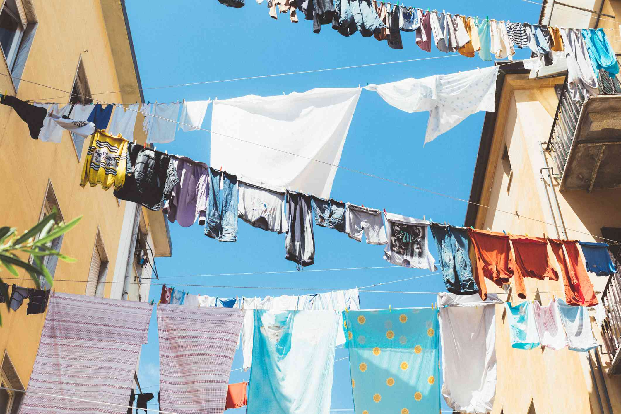 Clothes hanging on lines stretching across buildings.