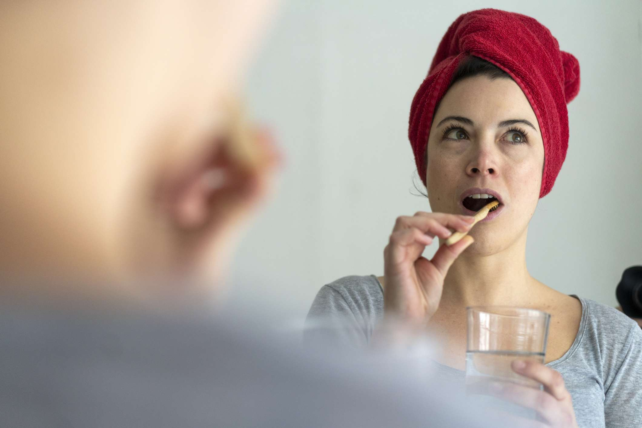 A woman brushes her teeth with a red towel on her head.