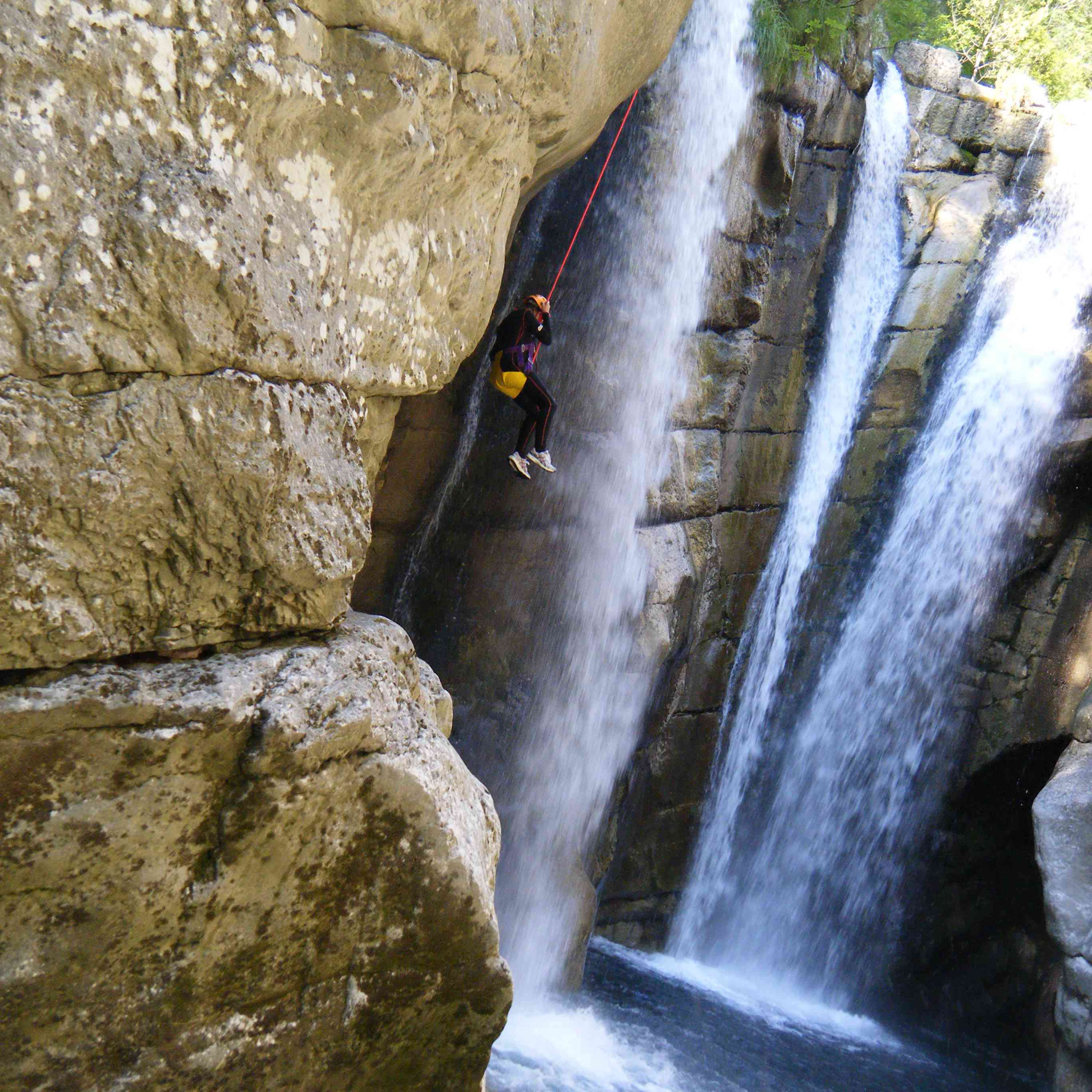 A woman descends into a waterfall while canyoning