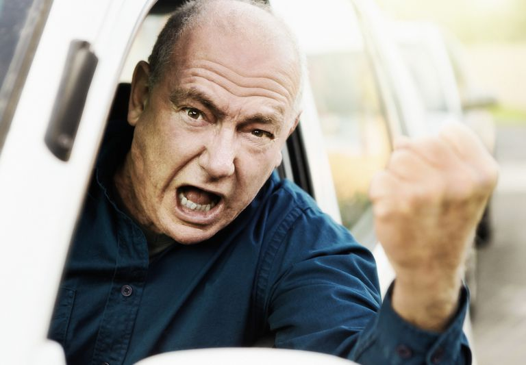Shouting senior man with road rage shakes his fist from his car