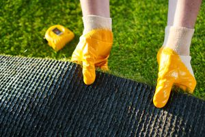 Artificial grass being rolled out as a lawn.