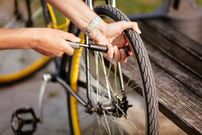 Close-up of a man pumping bicycle wheel on the street