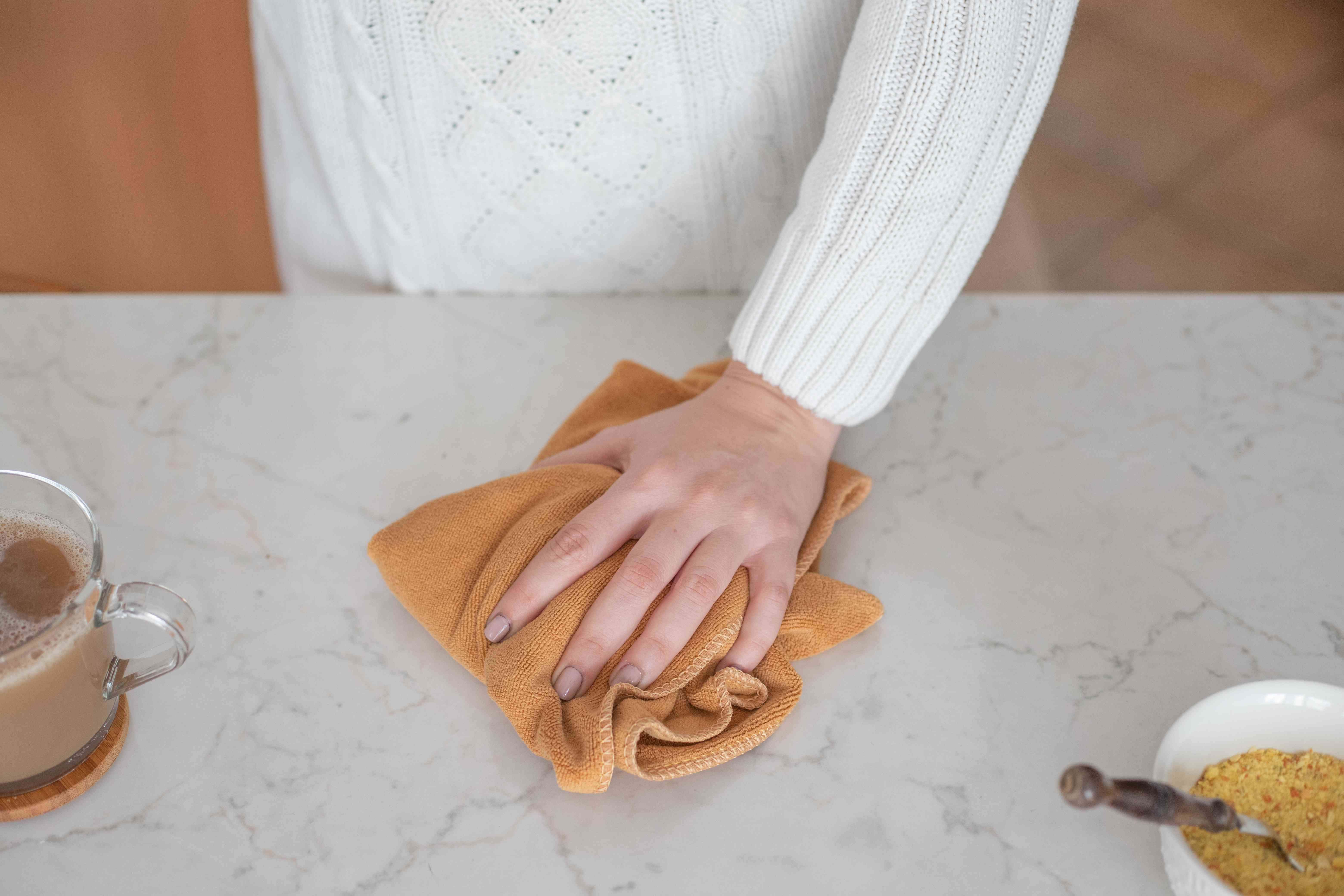 hands scrub kitchen with towel near cup of tea and food