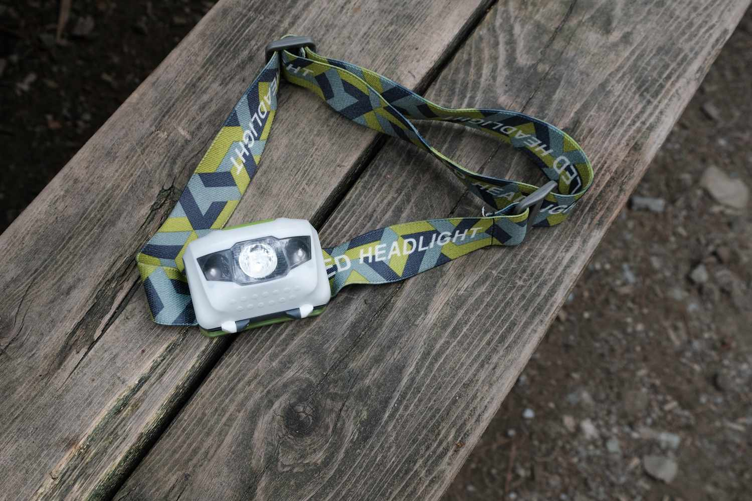 a headlamp rests on wooden picnic bench, ready for nighttime camping