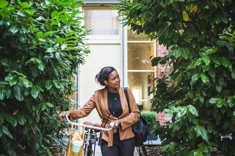 A Black woman pushes a bike and is surrounded by greenery.