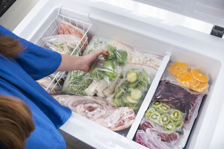 A woman puts vegetables in a chest freezer.
