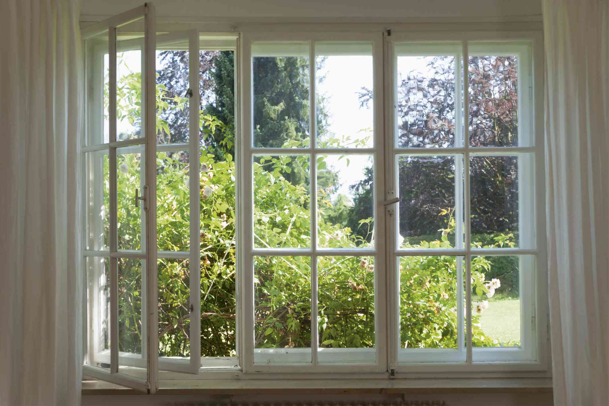 A white grid window is open and looks onto green landscape.