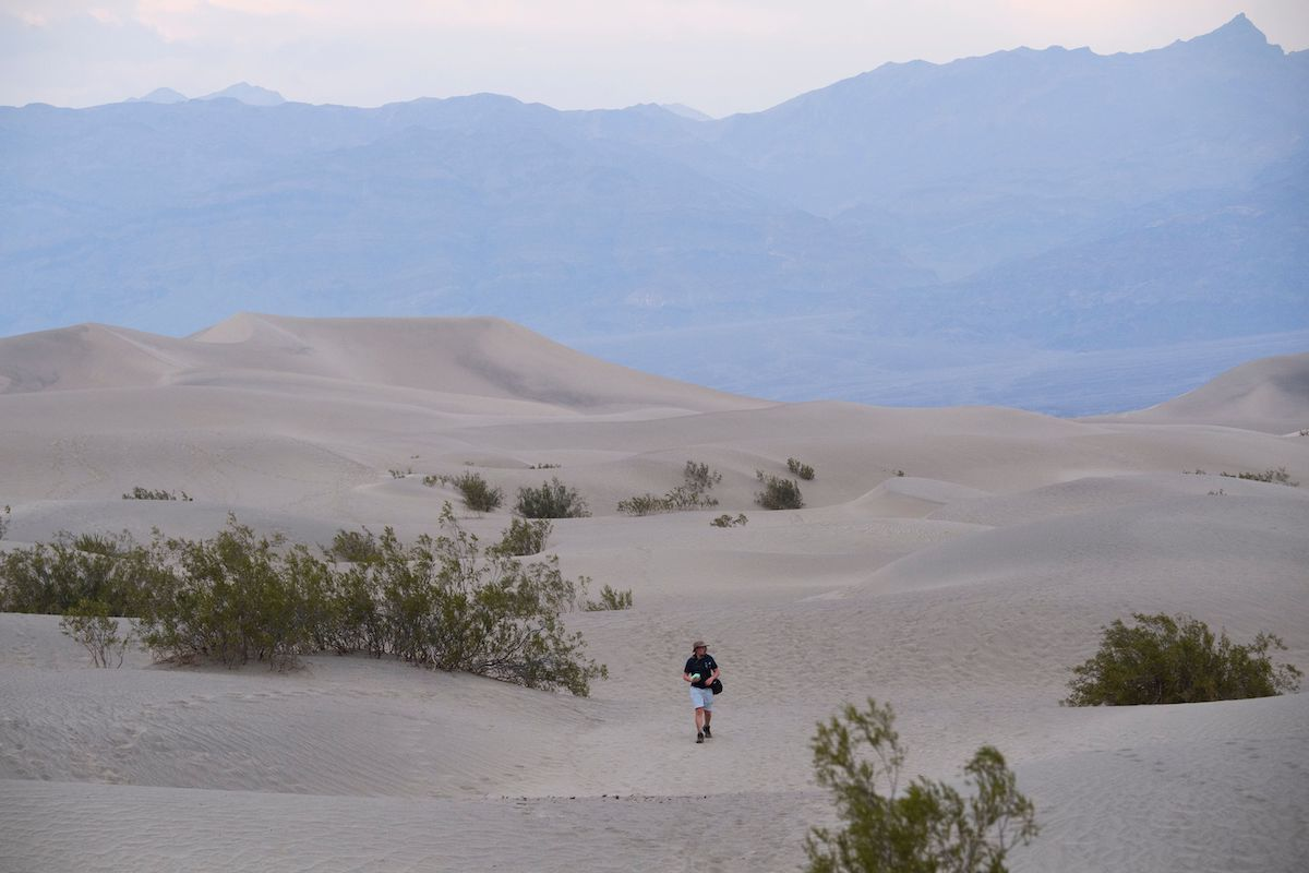 Visitors walk along sand dunes at sunset inside Death Valley National Park in June 17, 2021 in Inyo County, California.