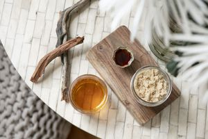 overhead shot of diy lip scrub with vanilla extract, honey, and brown sugar on tiled table