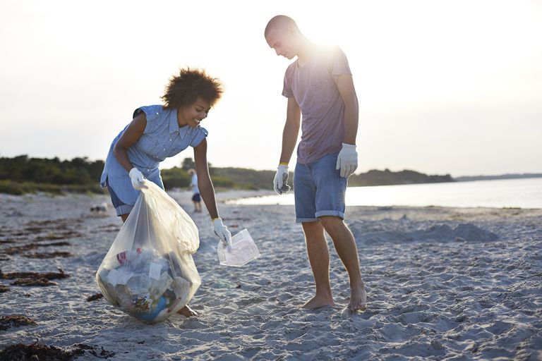 Two people collecting trash on a beach