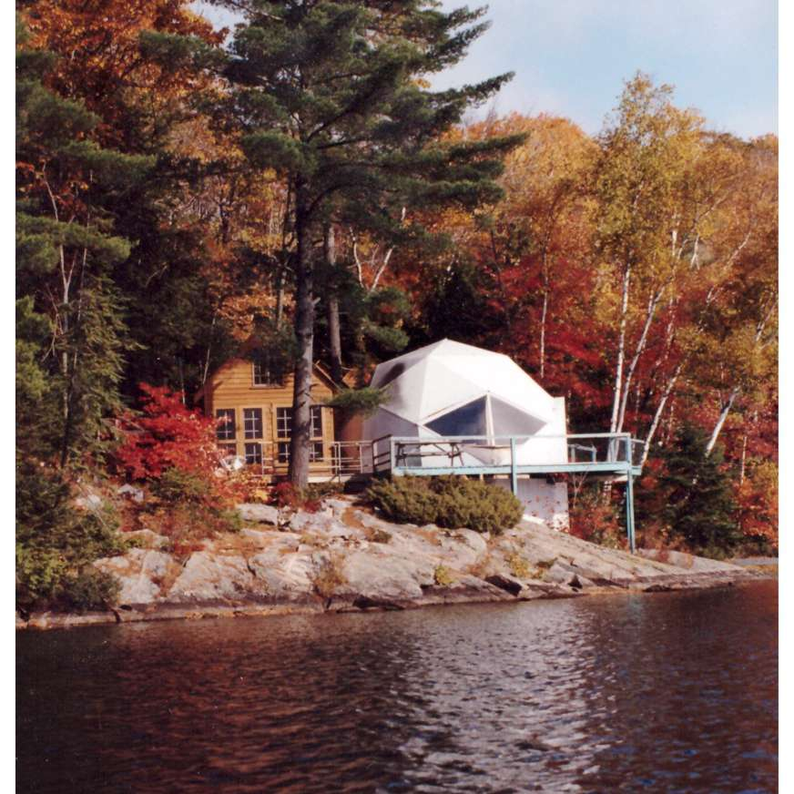 Dome next to a cabin, surrounded by trees, with a lake in the foreground
