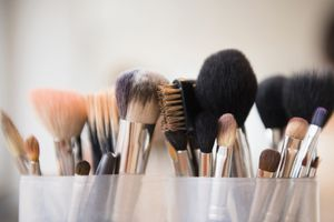 Close-up of makeup brushes propped up in cups