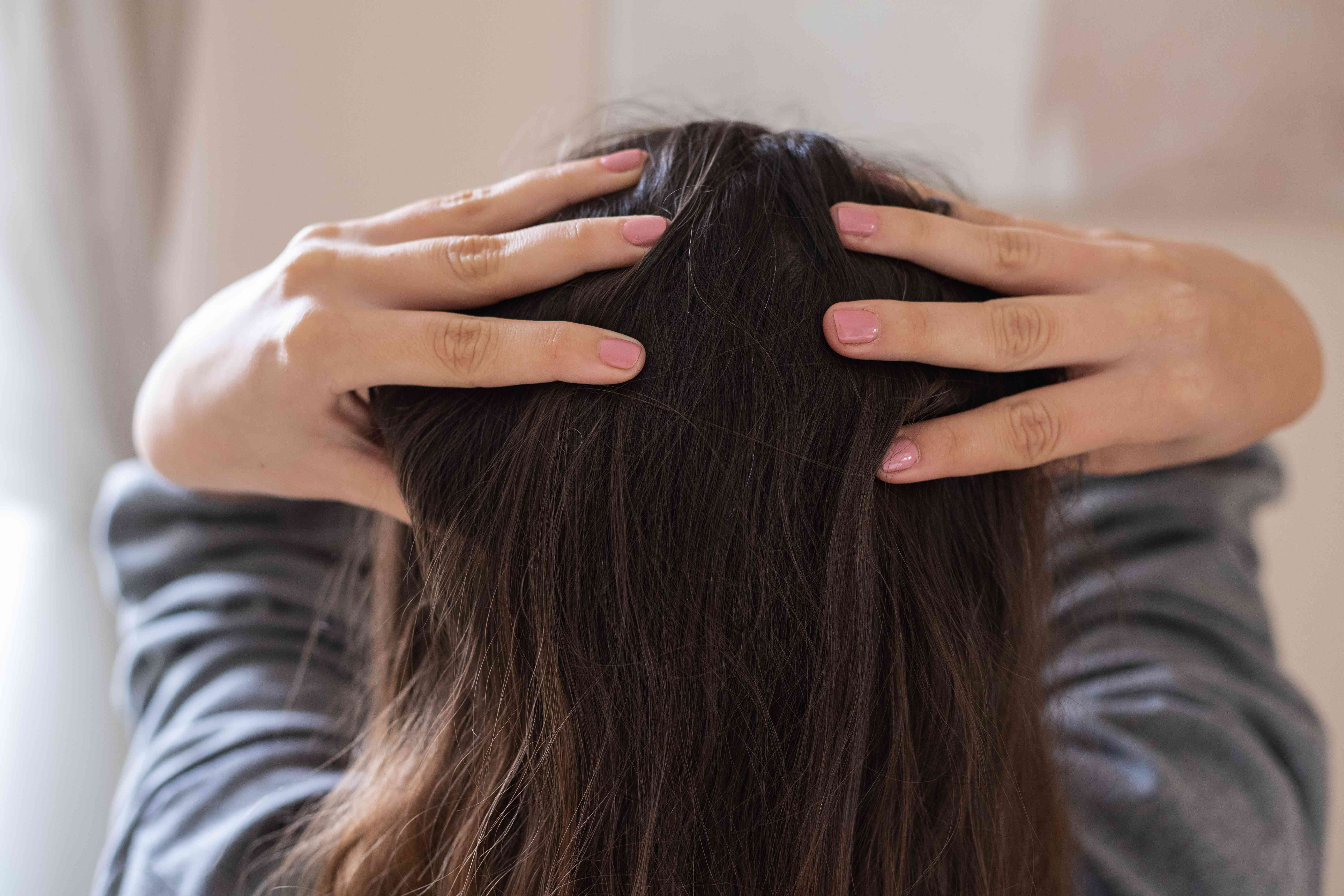 behind shot of woman with long brown hair giving herself scalp massage