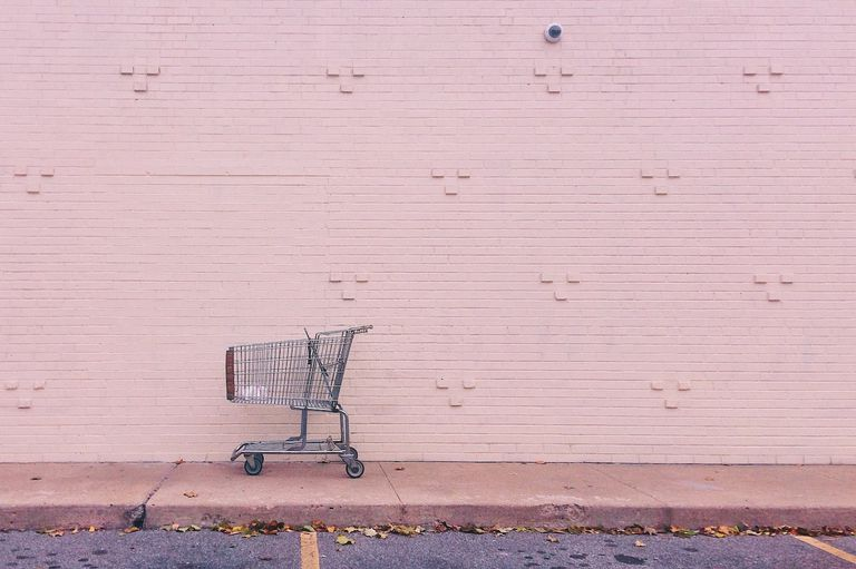 empty shopping car against pink brick wall