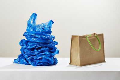 stack of plastic bags next to one reusable bag
