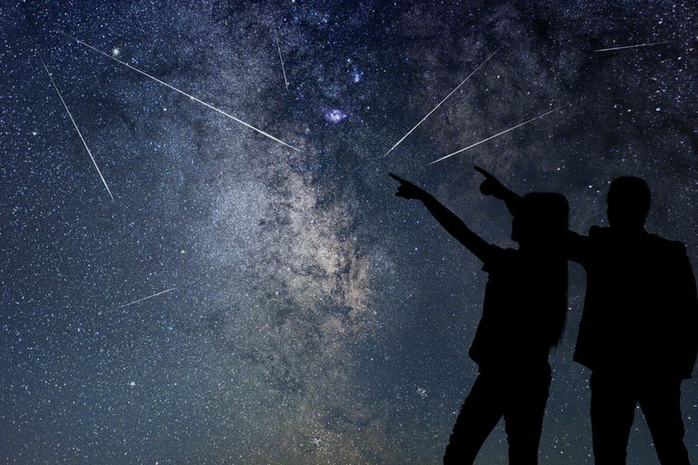 Two people silhouetted against a sky during a meteor shower