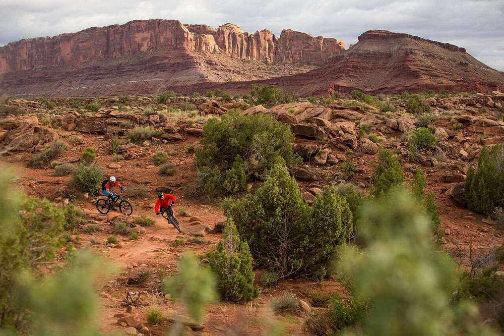 Two mountain bikers round a sharp corner on a trail in the Utah desert