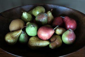 variety of pears in dark wooden bowl: asian, bartlett, anjou, seckel pears