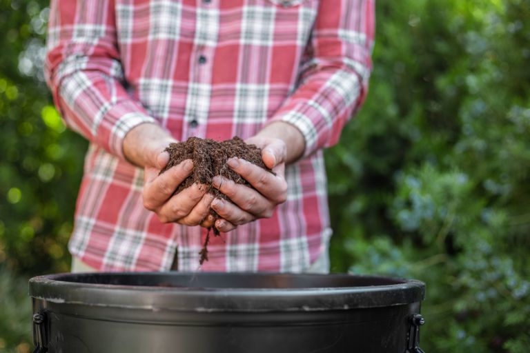 person in red plaid shirt stands over compost bucket holding dirt with bare hands